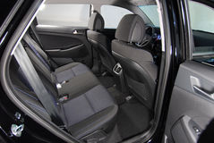 An open door of a black sedan showing off it's leather interior.